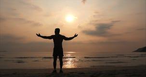 Athlet des jungen Mannes, der in Richtung der Sonne, gegen den Sonnenuntergang, tropischer Hintergrund blickt Gesundheit, Sport,  stock video