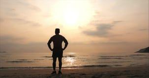 Athlet des jungen Mannes, der in Richtung der Sonne, gegen den Sonnenuntergang, tropischer Hintergrund blickt Gesundheit, Sport,  stock video footage