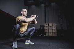 Athlet Doing Exercise With Clubbel an der Turnhalle lizenzfreies stockfoto