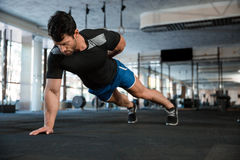 Athlet doing one hand push-ups. Athlet wearing blue shorts and black t-shirt doing one hand push-ups stock photos