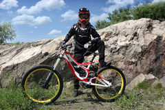 Athlet in einem Sturzhelm, der eine Mountainbike auf das Hinterrad reitet Stockfotografie