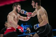 Athlet gemischter Kampfkunstkämpfer gelangt Querhand an seinen Gegner Lizenzfreie Stockfotos