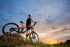 Athlet i hjälmen som står nära cykeln och att posera royaltyfria bilder
