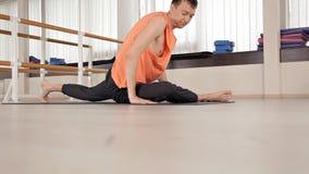 Athlet-Mann macht die Torsowendungen und sitzt auf dem Boden in der Turnhalle, Yoga?bungen Gesundheit, Leben, Flexibilit?t stock video footage