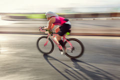 Athlet riding bicycle. Female athlet riding bicycle at sunny day on coastal road, blurred motion. Person is not recognizable royalty free stock images