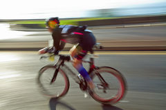 Athlet riding bicycle. At sunny day on coastal road, blurred motion royalty free stock photos