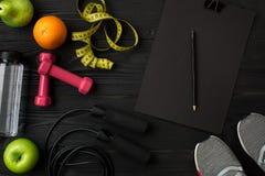 Athlet ` s stellte mit weiblicher Kleidung, Turnschuhen und Flasche Wasser auf dunklem Hintergrund ein Stockfotos