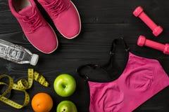 Athlet ` s stellte mit weiblicher Kleidung, Turnschuhen und Flasche Wasser auf dunklem Hintergrund ein Stockfoto