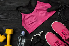 Athlet ` s stellte mit weiblicher Kleidung, Turnschuhen und Flasche Wasser auf dunklem Hintergrund ein Lizenzfreie Stockfotos