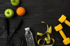 Athlet ` s stellte mit weiblicher Kleidung, Turnschuhen und Flasche Wasser auf dunklem Hintergrund ein Lizenzfreies Stockbild