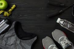 Athlet ` s stellte mit weiblicher Kleidung, Turnschuhen und Flasche Wasser auf dunklem Hintergrund ein Stockbild