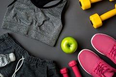 Athlet ` s stellte mit weiblicher Kleidung, Turnschuhen und Flasche Wasser auf grauem Hintergrund ein Stockbilder