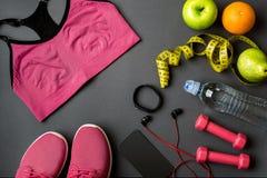 Athlet ` s stellte mit weiblicher Kleidung, Turnschuhen und Flasche Wasser auf grauem Hintergrund ein Stockfotos
