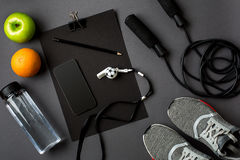 Athlet ` s stellte mit weiblicher Kleidung, Turnschuhen und Flasche Wasser auf grauem Hintergrund ein Lizenzfreies Stockbild