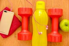 Athlet ` s stellte mit zwei rosa Dummköpfen, smarphone mit rosa Kopfhörern, grünem appple und einer gelben Flasche Wasser, in a e stockfotos