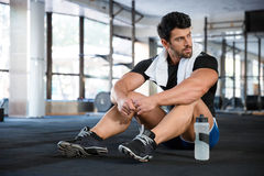 Athlet sitting on the floor in gym. Athletic man wearing blue shorts and black t-shirt sitting on the floor in gym stock image