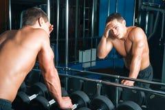 Athlet am Spiegel berührt seinen Kopf Stockbilder