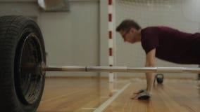 Athlet spinge verso l'alto dal pavimento di legno vicino al bilanciere archivi video