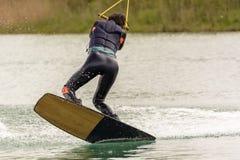 Athlet Woman ist Wakeboarding am Kabel-Park lizenzfreie stockfotografie
