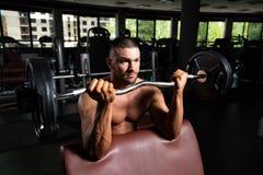 Athlet Working Out Biceps in einer Turnhalle lizenzfreie stockbilder
