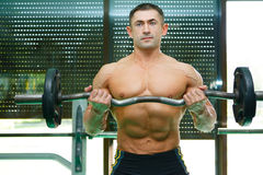 Athlete. The young sports guy trains in a gym lifting a bar Royalty Free Stock Photos