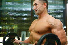 Athlete. The young sports guy trains in a gym lifting a bar Royalty Free Stock Images