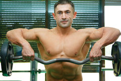 Athlete. The young sports guy trains in a gym lifting a bar Royalty Free Stock Photo
