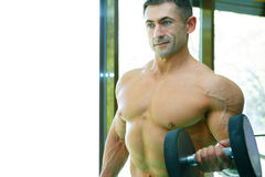 Athlete. The young sports guy trains in a gym lifting dumbbells Royalty Free Stock Photography
