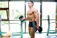 Athlete. The young sports guy trains in a gym lifting dumbbells Royalty Free Stock Photos