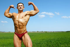 Athlete. The young sports guy poses against the nature Royalty Free Stock Images