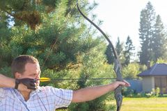 Athlete aiming at a target and shoots an arrow. Archery. Banner stock photo