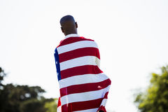Athlete with american flag wrapped around his body Royalty Free Stock Images
