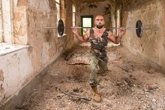 Man With Barbell Exercising Legs In Refuge Stock Image