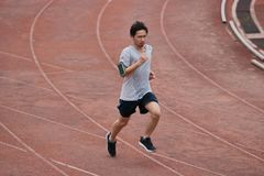 Athlete Asian man running on racetrack in stadium . Healthy active lifestyle concept. Athlete Asian man running on racetrack in stadium . Healthy active Stock Photo