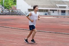 Athlete Asian man running on racetrack in stadium. Healthy active lifestyle concept. Athlete Asian man running on racetrack in stadium. Healthy active lifestyle Royalty Free Stock Photography