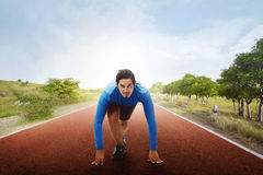 Athlete asian man on starting line ready to running. With blue sky background Stock Photography