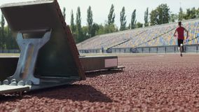 Athlete beginning to run from starting blocks at competition, slow-motion stock video footage