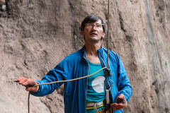 Athlete belays Climber using belaying device and rope Royalty Free Stock Image