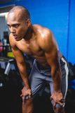 Athlete bending with hands on knee. Shirtless athlete bending with hands on knee in gym Stock Photo