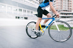 Athlete bicyclist rides against the backdrop of urban architecture. Man on a bright bike. Stock Images