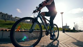 Athlete with a bionic leg is riding a bike along the road. 4K stock video footage
