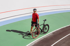 Athlete with a black bicycle at velodrome. Professional sports man in a red T-shirt and helmet Royalty Free Stock Images