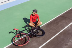 Athlete with a black bicycle at velodrome. Professional sports man in a red T-shirt and helmet Stock Photo