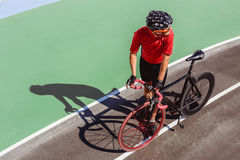 Athlete with a black bicycle at velodrome. Professional sports man in a red T-shirt and helmet Stock Photography