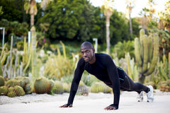 Athlete in black skin-tight suit pressed Royalty Free Stock Images