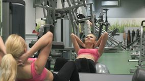 Athlete blonde engaged in the gym. Beautiful blond woman in sports clothes pump the abs muscles, make the leans forward and back looking at herself in the stock video