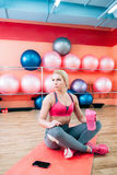 Athlete blonde sitting at gym with pensive look Stock Image