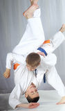 An athlete with a blue belt performs technique nage-waza Stock Photo