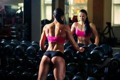 Athlete bodybuilder girl posing back in gym royalty free stock images