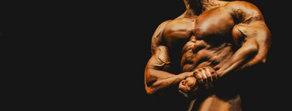 Athlete bodybuilder are sideways strain of thigh muscles at comp. Etition royalty free stock image